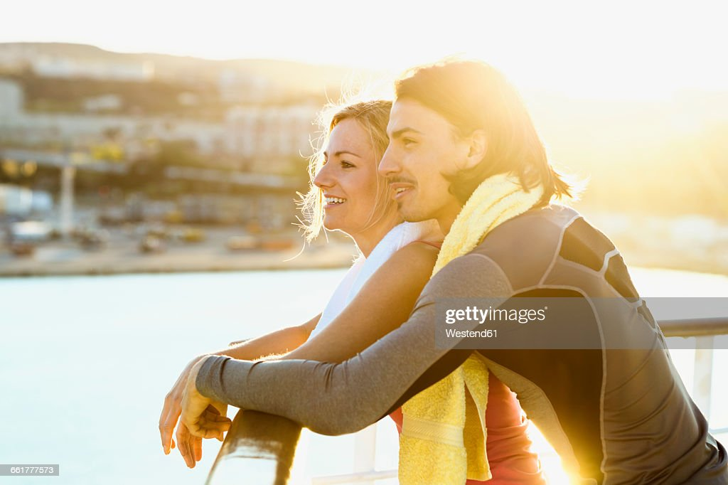 Happy couple standing on deck of a cruise liner looking at distance : Stock Photo