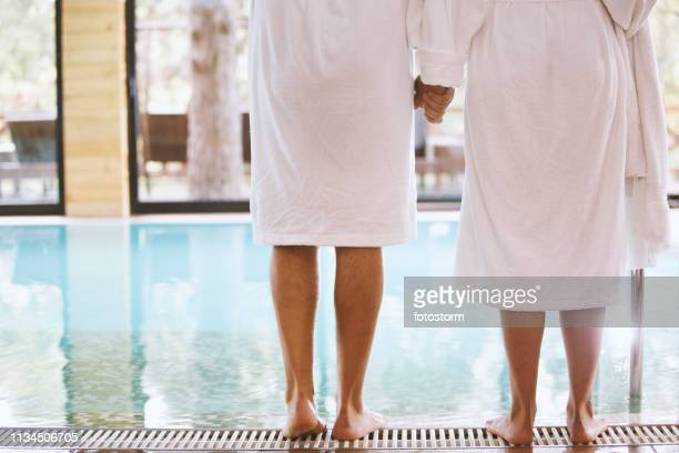 happy couple standing on poolside - health farm stock pictures, royalty-free photos & images