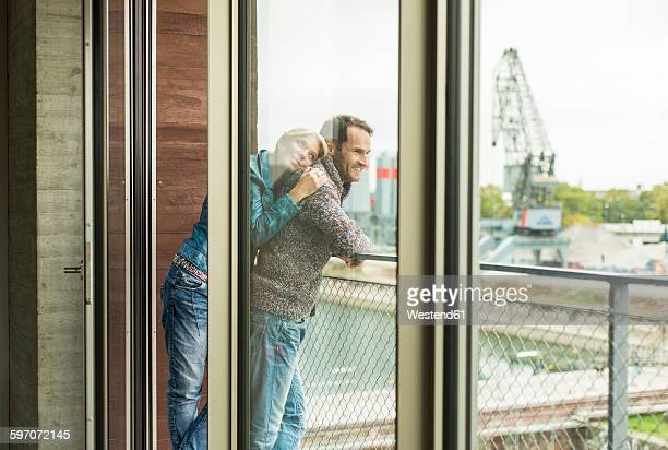 Happy couple standing together on balcony looking at distance