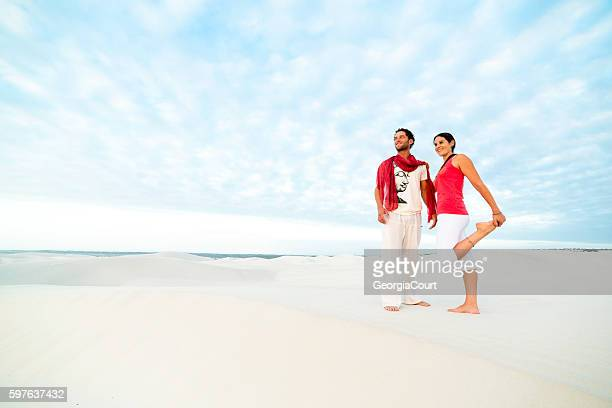 Happy couple stands on dune looking into sunrise