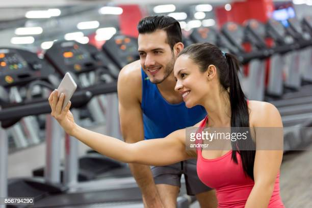 Happy couple taking a selfie at the gym