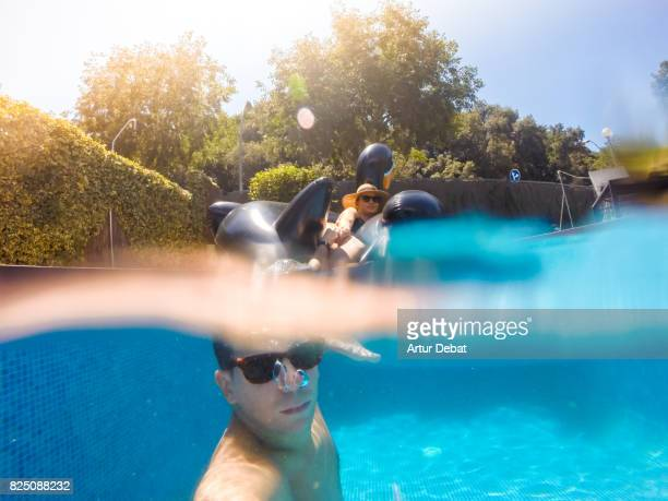 Happy couple taking a selfie enjoying summer in swimming pool with big inflatable black swan sunbathing and relaxing in the sun during weekend.
