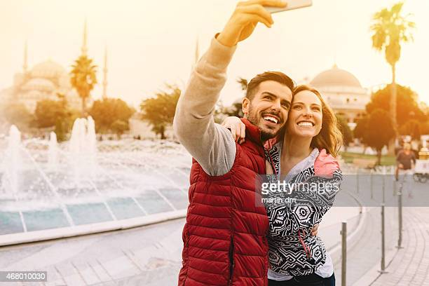 Happy couple taking a selfie in front of a fountain