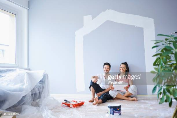 happy couple taking break from painting walls in new apartment - home improvement stock pictures, royalty-free photos & images