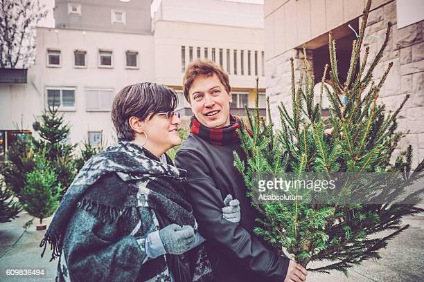 Glückliches Paar mit Weihnachtsbaum zu Hause, City Market, Europa