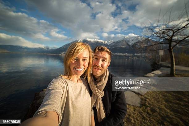 Happy couple taking selfie by the lake
