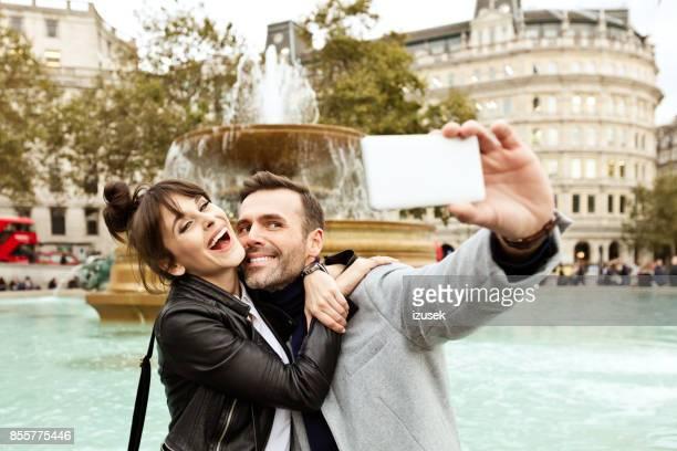 Brautpaar nehmen Selfie vor Brunnen am Trafalgar Square in London