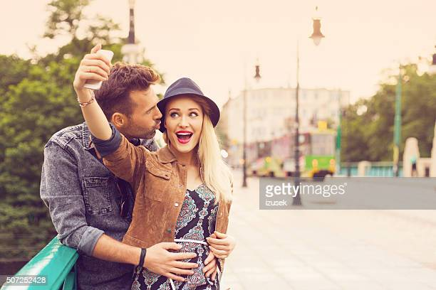 Happy couple taking selfie on the street, outdoor portrait
