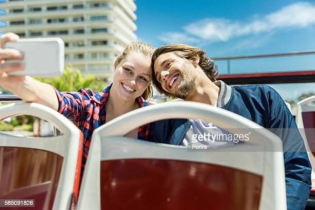Happy couple taking selfie sitting in tour bus
