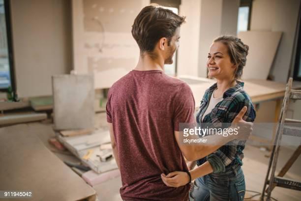 Heureux couple parler les uns aux autres à leur rénovation appartement.