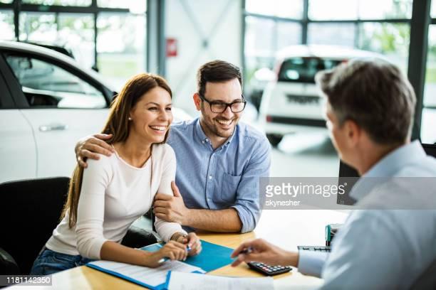 pares felizes que falam ao vendedor em uma reunião em uma sala de exposições do carro. - new - fotografias e filmes do acervo
