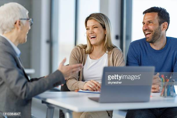 happy couple talking to their agent on a meeting in the office. - mortgage stock pictures, royalty-free photos & images