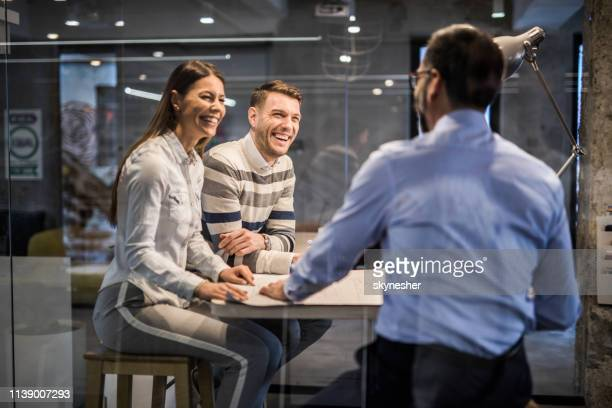 Happy couple talking to their financial advisor in the office.