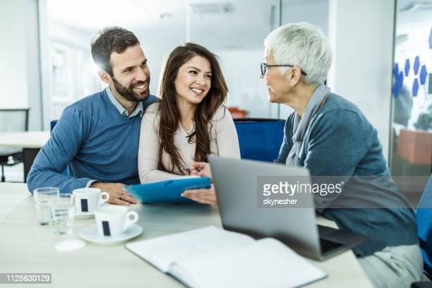 happy couple talking to their insurance agent on a meeting in the office. - financial advisor stock pictures, royalty-free photos & images