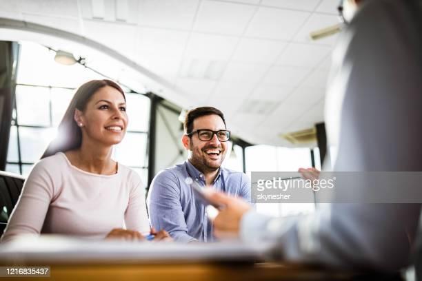 glückliches paar im gespräch mit ihrem versicherungsvertreter bei einem treffen im büro. - beratung stock-fotos und bilder