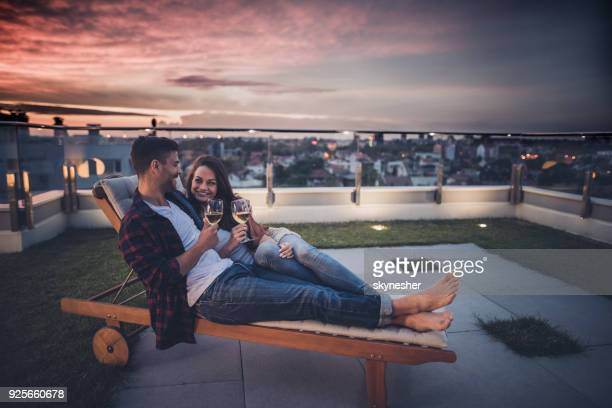 happy couple talking while enjoying in wine on a penthouse terrace at twilight. - penthouse stock pictures, royalty-free photos & images