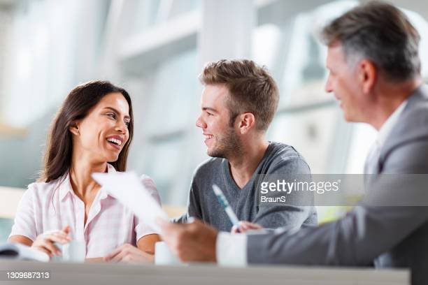 happy couple talking while having a meeting with their agent in the office. - mortgage stock pictures, royalty-free photos & images