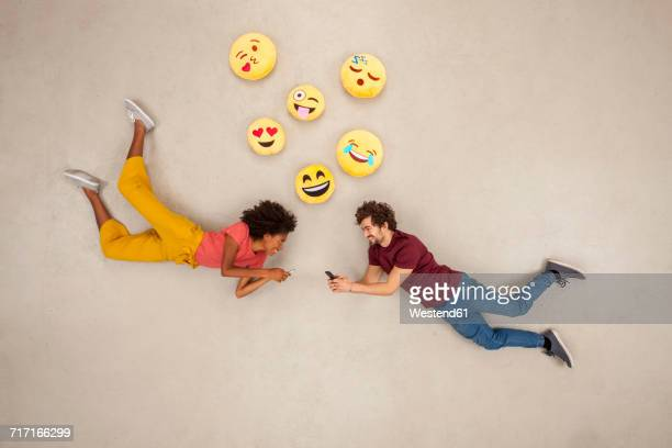 happy couple texting on their smart phones, sending emojies - dating stock-fotos und bilder