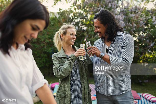 Happy couple toasting drink bottles during summer party in yard