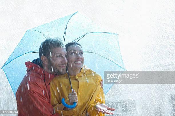 Happy couple under umbrella in rain