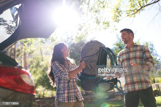 happy couple unpacking a backpack from their car - packing stock pictures, royalty-free photos & images