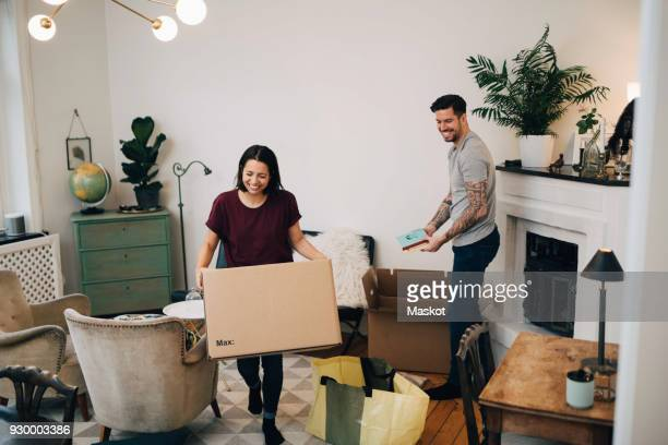 happy couple unpacking boxes in living room at new home - unpacking stock pictures, royalty-free photos & images