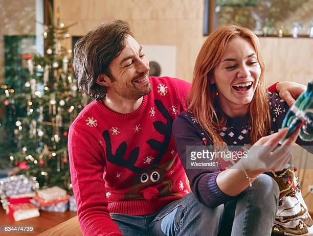Happy couple unwrapping childrens shoes in front of Christmas tree