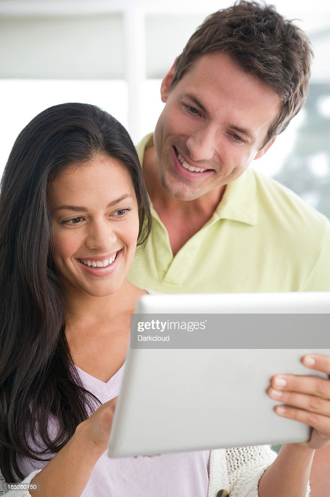Happy couple using a digital tablet : Stock Photo