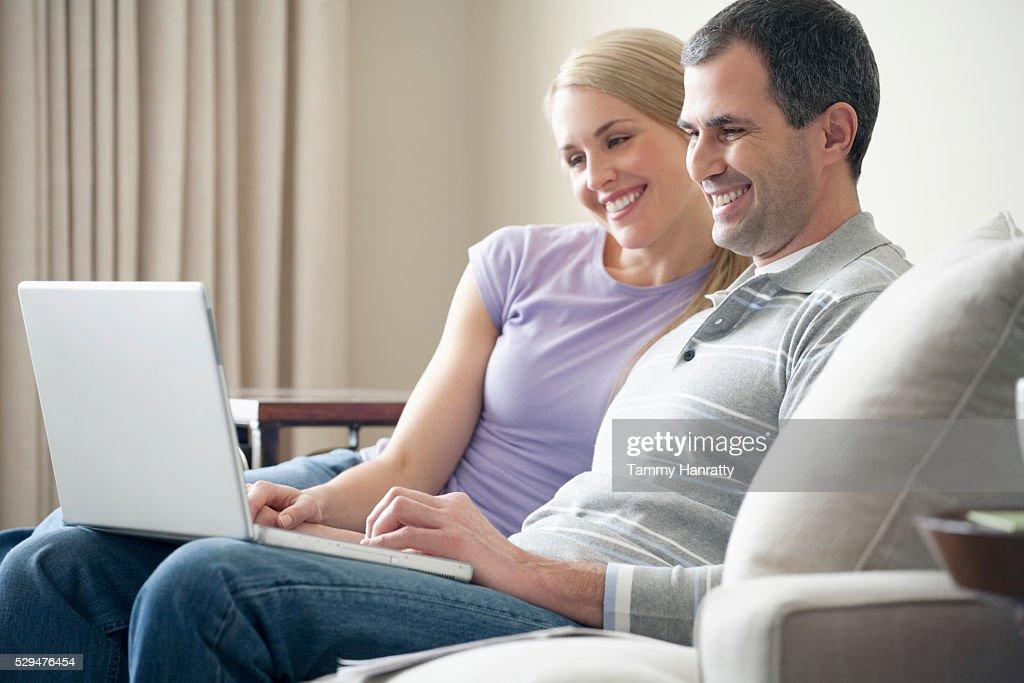 Happy couple using a laptop : Foto de stock
