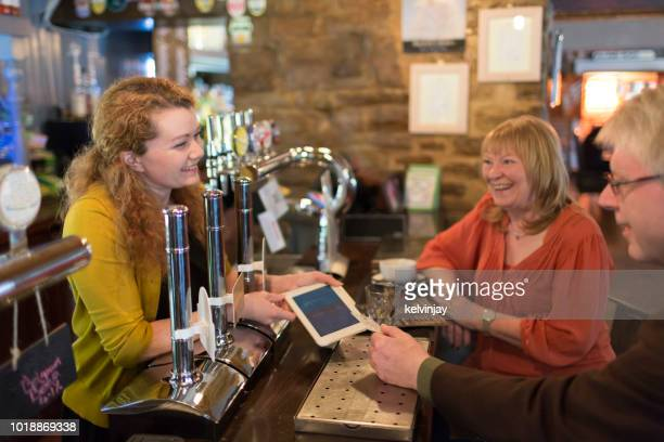 Happy couple using contactless card payment to pay the bill in a restaurant bar