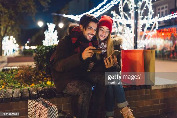 Happy couple using credit card for online shopping