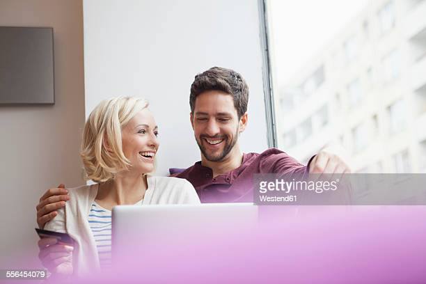 Happy couple using digital tablet for online shopping