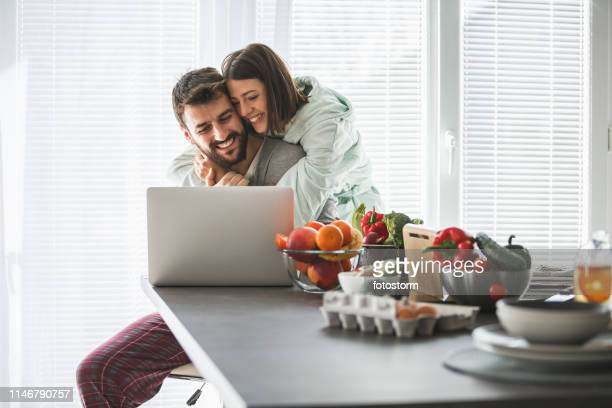 happy couple using laptop at home in the morning - love is blind stock pictures, royalty-free photos & images