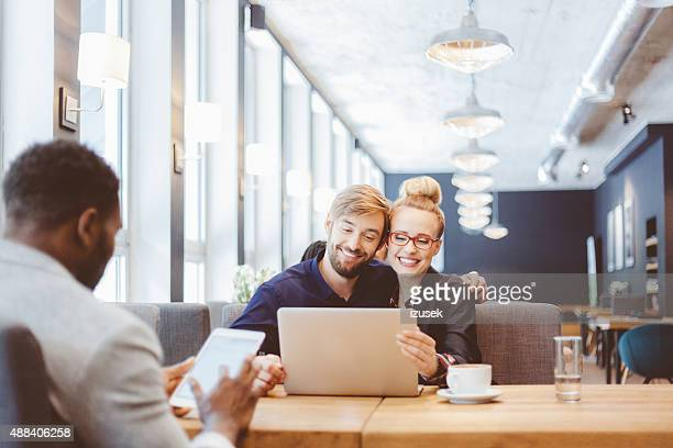 Happy couple using laptop together in the restaurant