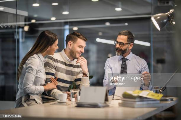 happy couple using laptop with their insurance agent in the office. - customer stock pictures, royalty-free photos & images