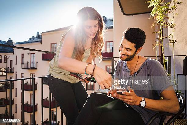 Happy couple using smart phone while reading guidebook on balcony