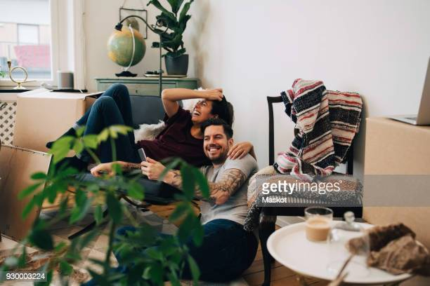 happy couple using smart phone while resting at new home during location - besonderes lebensereignis stock-fotos und bilder