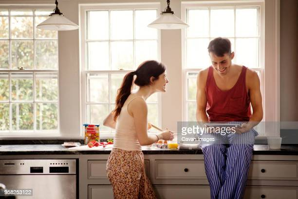 happy couple using tablet computer while cooking in kitchen at home - hair back stock pictures, royalty-free photos & images
