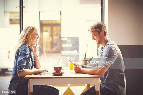 Happy couple using technologies and laughing in trendy cafe