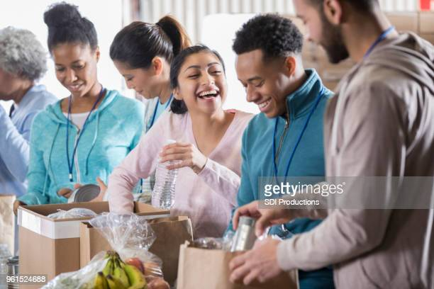 happy couple volunteer in community food bank - charitable donation stock pictures, royalty-free photos & images