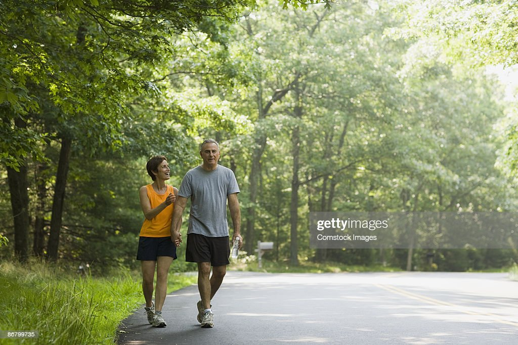Happy couple walking along road together : Stock Photo