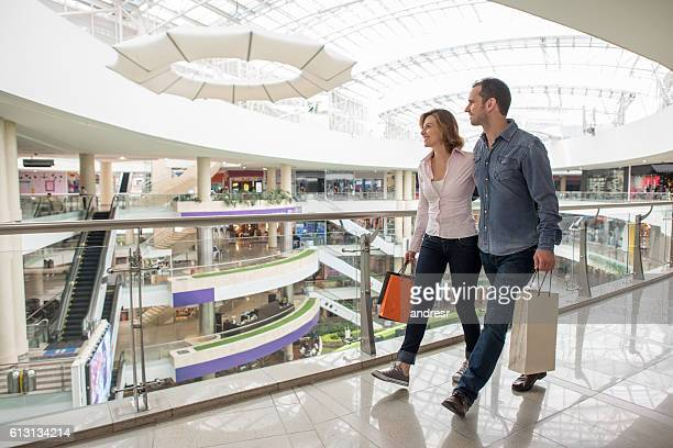 happy couple walking at the shopping center - shopping centre stock photos and pictures