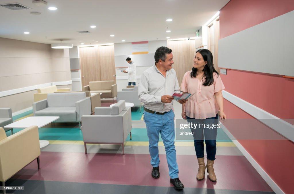 Glückliches Paar zu Fuß entfernt von nach Rücksprache mit Arzt beide sprechen und Lächeln : Stock-Foto