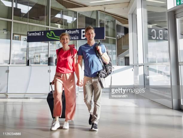 happy couple walking hand in hand at the airport - ankunft stock-fotos und bilder
