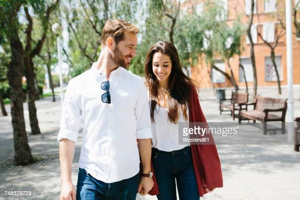 Happy couple walking in the street, holding hands