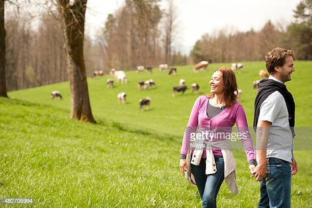 Happy couple walking on a meadow near pasture