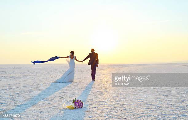 happy couple walking on snow - utah wedding stock pictures, royalty-free photos & images