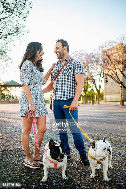 Happy couple walking their dogs