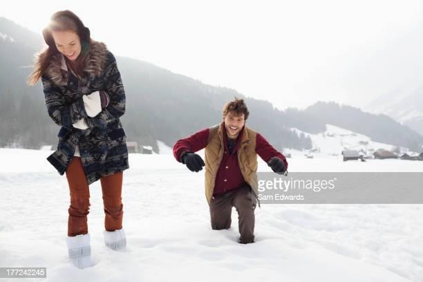 Feliz pareja caminando a través de nieve en profundidad de campo