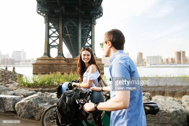 happy couple walking with bicycle by manhattan bridge against sky - casal heterossexual - fotografias e filmes do acervo